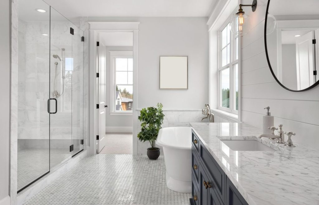 Modern and sleek master bathroom with marble vanity and walk in shower backsplash