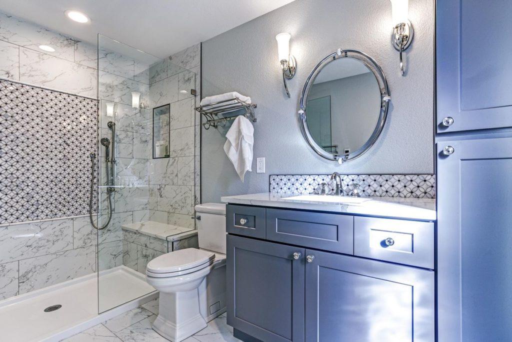 Dark gray vanity with white quartz countertop and marble backsplash sit in shower