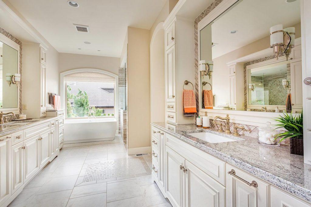 Classic quartz vanities with gold hardware and elegant porcelain tile backsplash