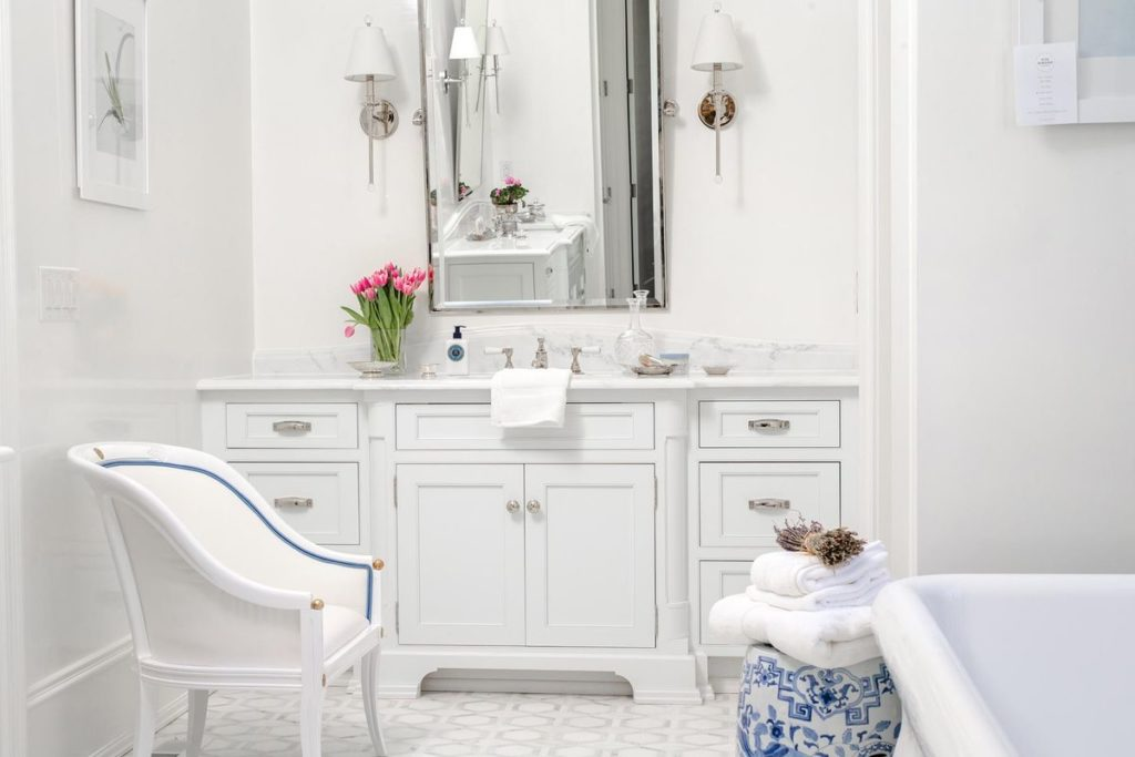 All white bathroom with classic marble vanity and freestanding bath