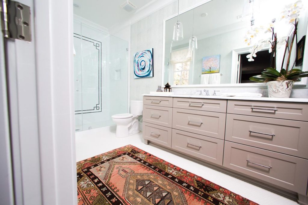 Walk in shower with porcelain backsplash, taupe vanity and marble countertop