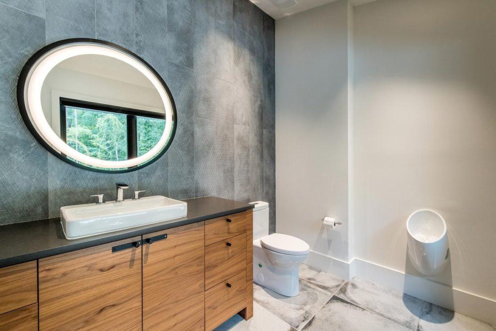 Modern wooden vanity with dark quartz countertop and porcelain tile backsplash