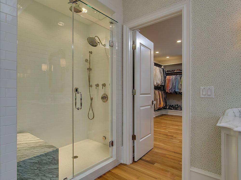 Walk in shower with white subway tile backsplash and hardwood floors