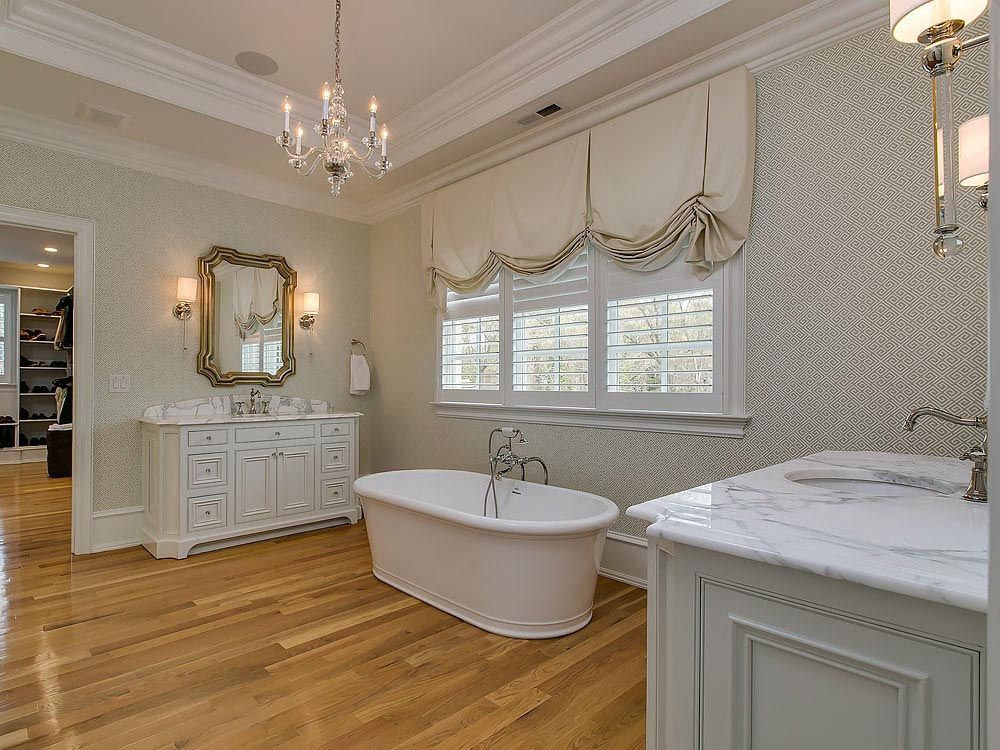 Gorgeous hardwood floored master bathroom with stand alone tub and marble vanity