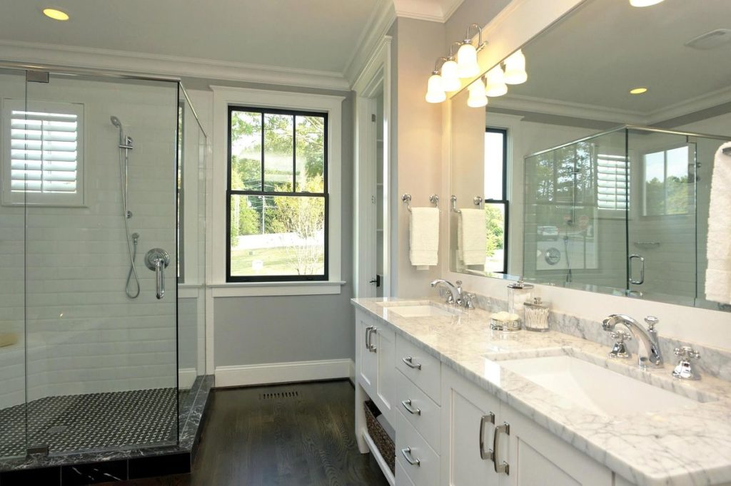 Walk in shower with subway tile backsplash and white double vanity with quartz countertop