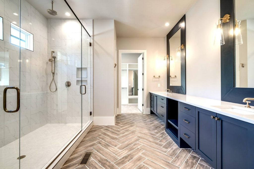 Modern master bathroom with navy blue vanity with white quartz countertops