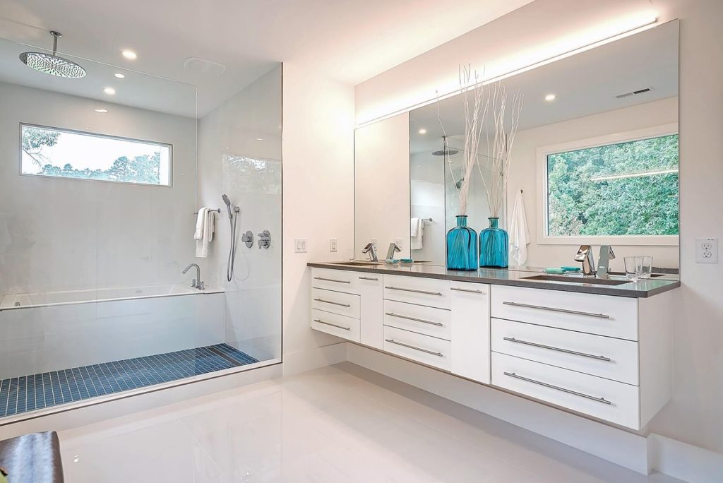 Modern master bathroom with blue tile and floating white vanity with quartz countertop