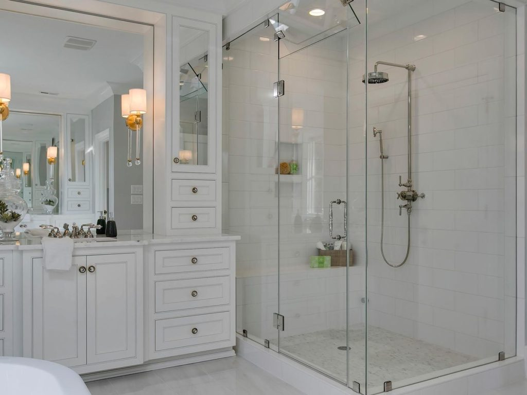 Large walk in shower with white porcelain tile and brushed nickel hardware