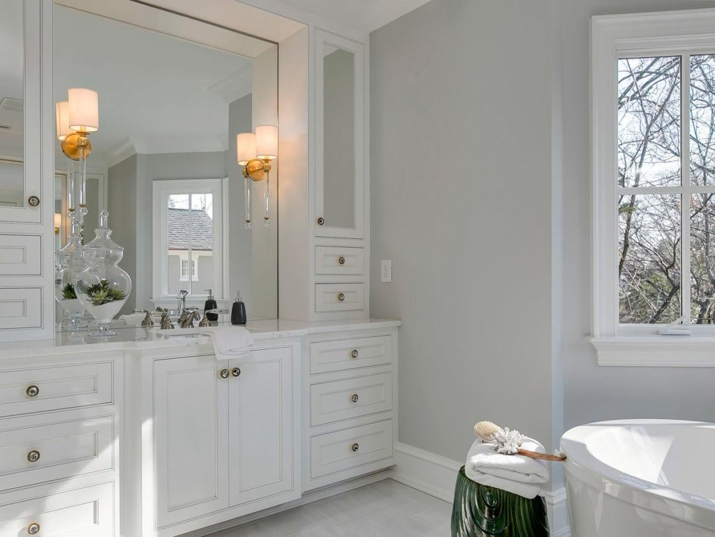 Large built in white vanity with quartz countertop and brushed nickel hardware