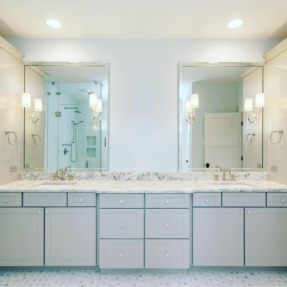 Light grey double vanity with marble countertop and gold hardware