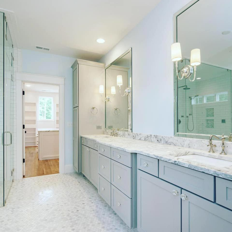 Double vanity with marble countertop and subway tile walk in shower