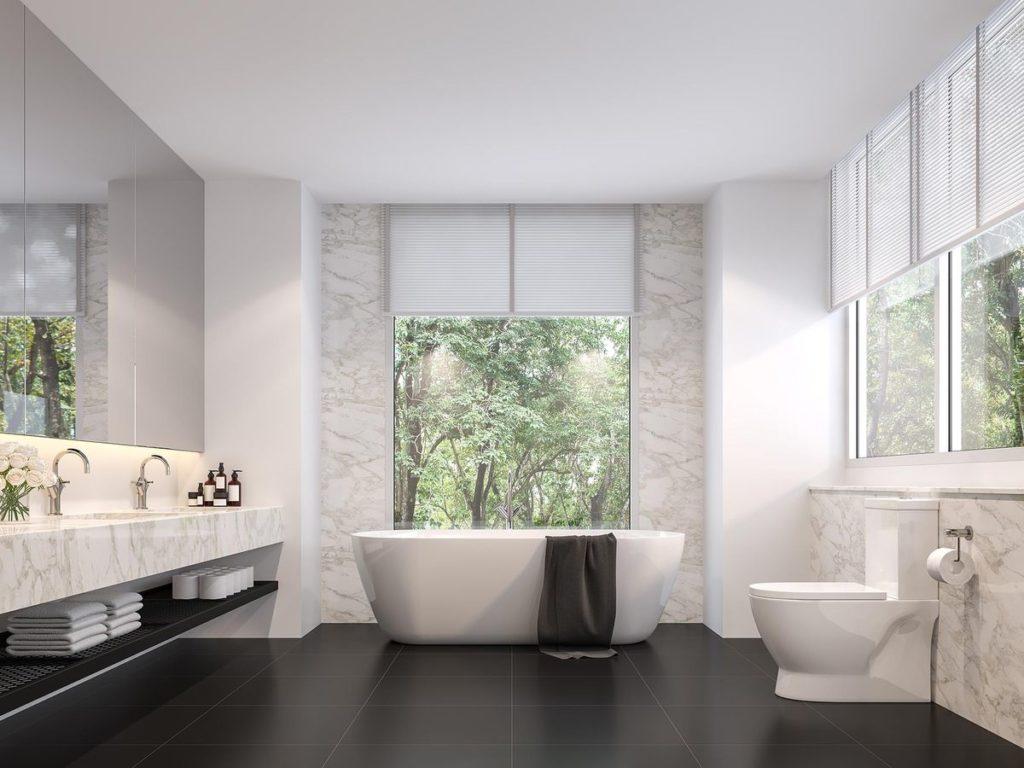 Master bathroom suite with freestanding tub with marble backsplash