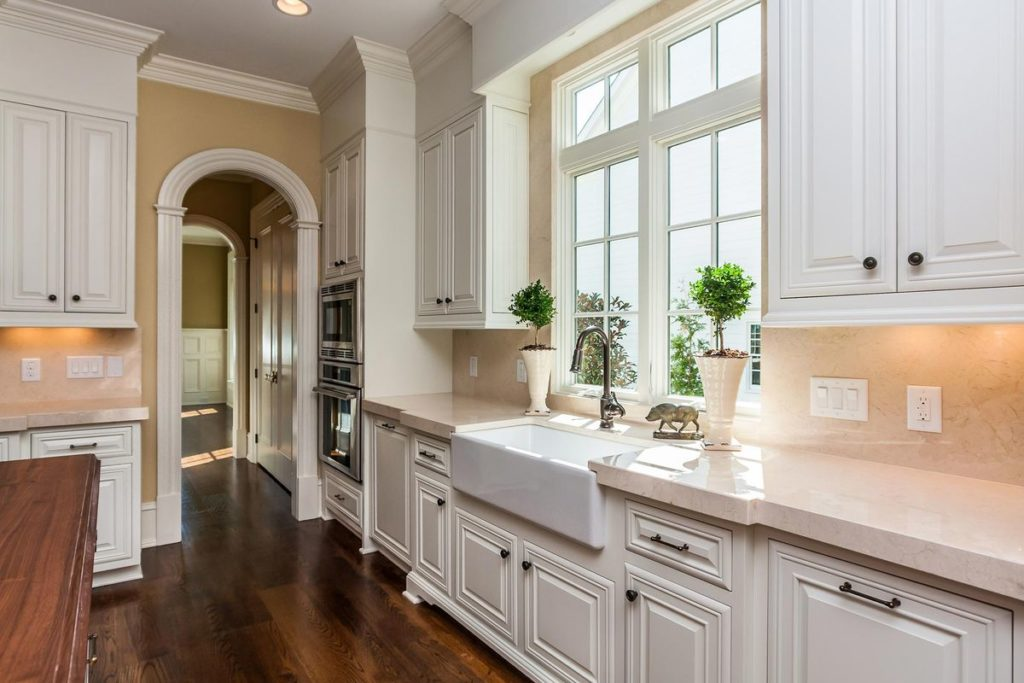 Kitchen with white farmhouse sink and elegant pink granite countertops