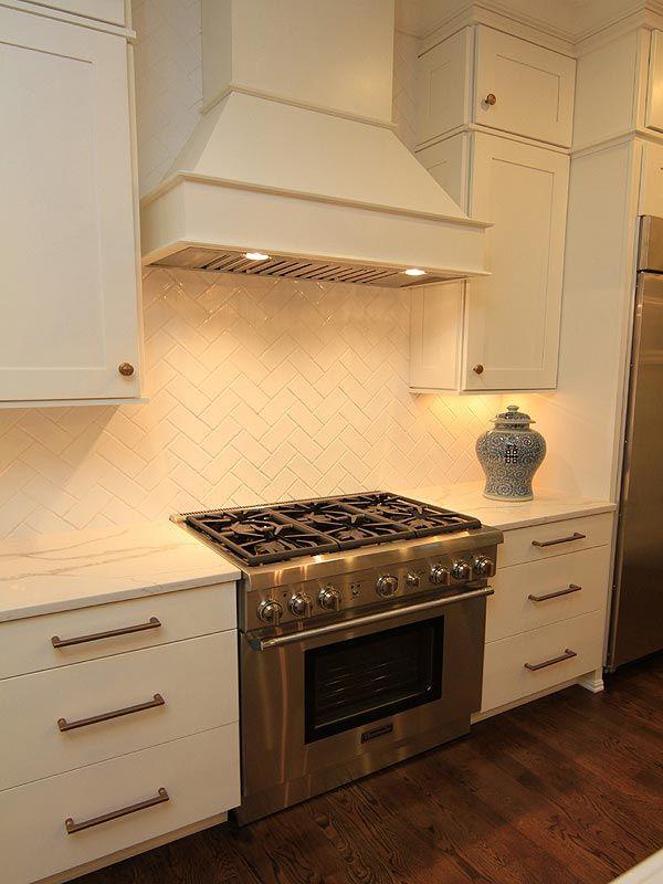 Oven with white hood, white tile backsplash and granite countertop