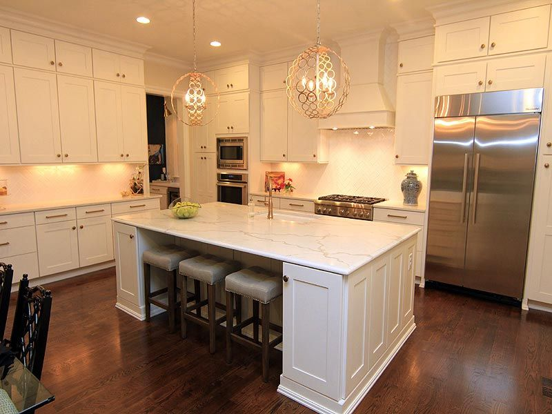 White kitchen cabinets with porcelain tile backsplash and white granite countertops