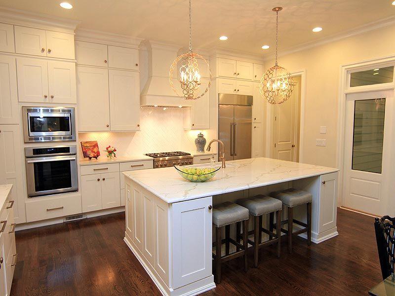 White kitchen island with gold hardware and white granite countertop