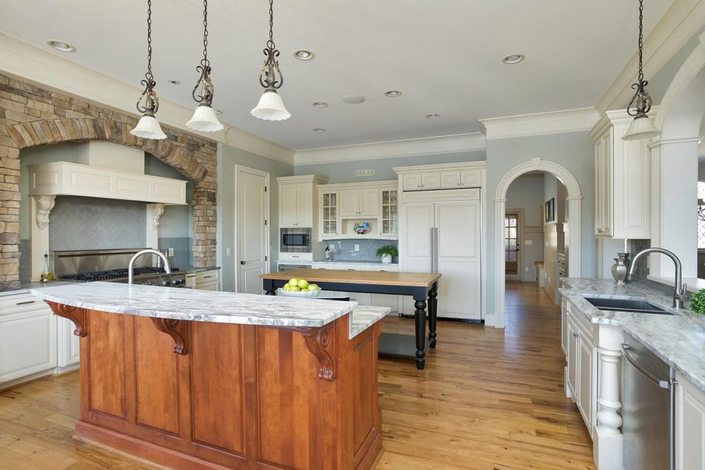 Teak stained kitchen island with granite countertop and bar nook
