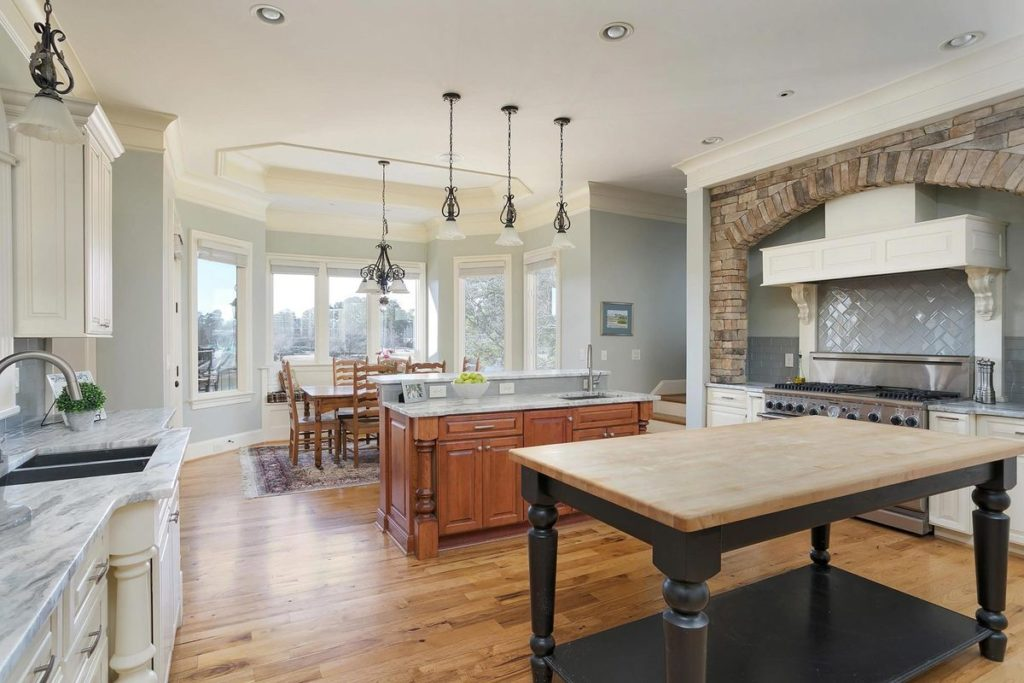 Butcher block kitchen table with craftsman stained wood island and silver blue granite countertops