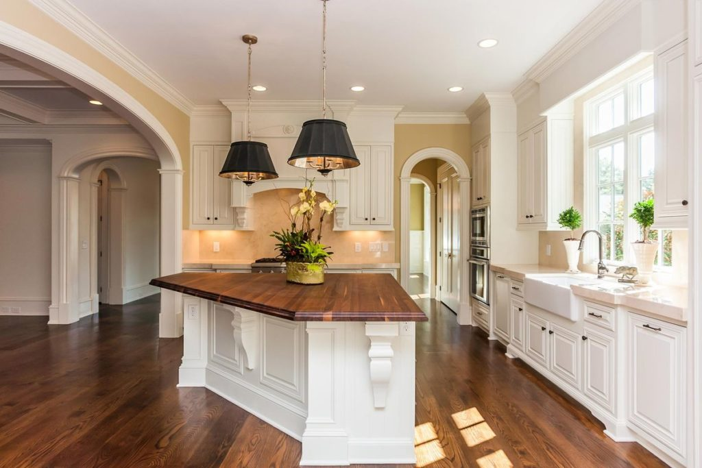 White kitchen featuring triangular wood topped island and pink granite countertops