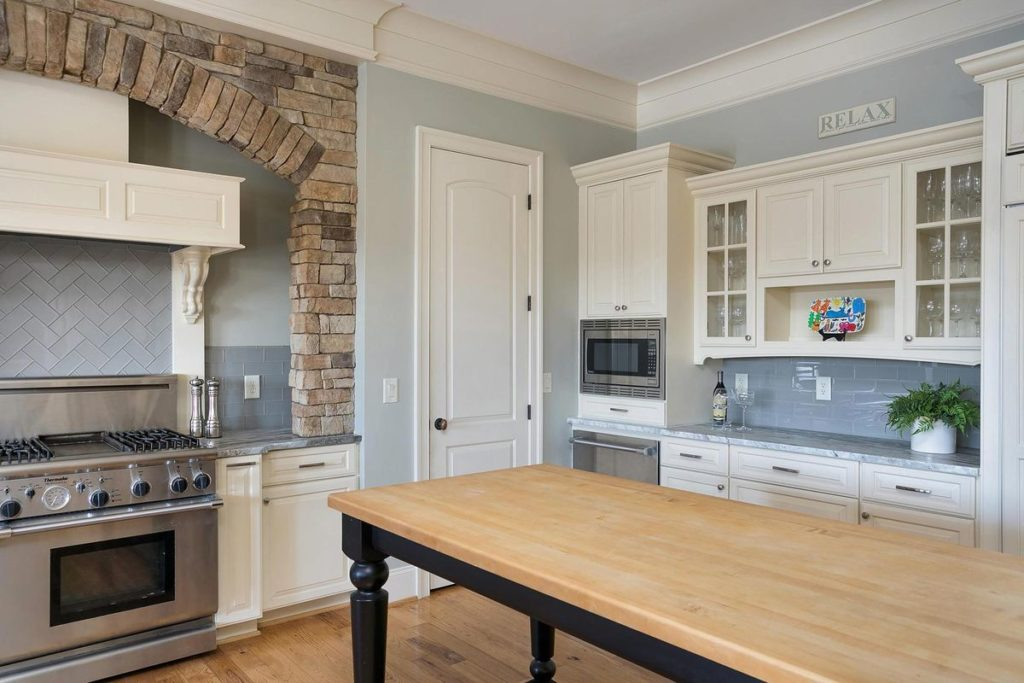 Farmhouse kitchen with white cabinets, silver blue granite countertops, and light blue tile backsplash