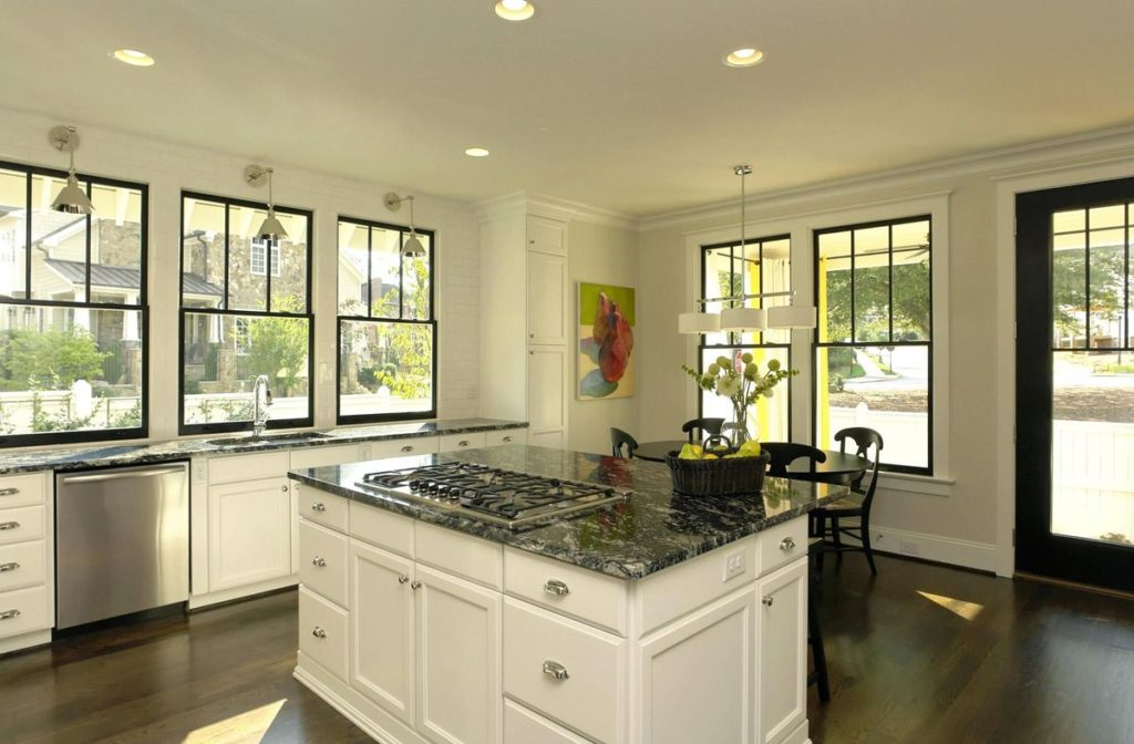 White kitchen island with dark granite countertop