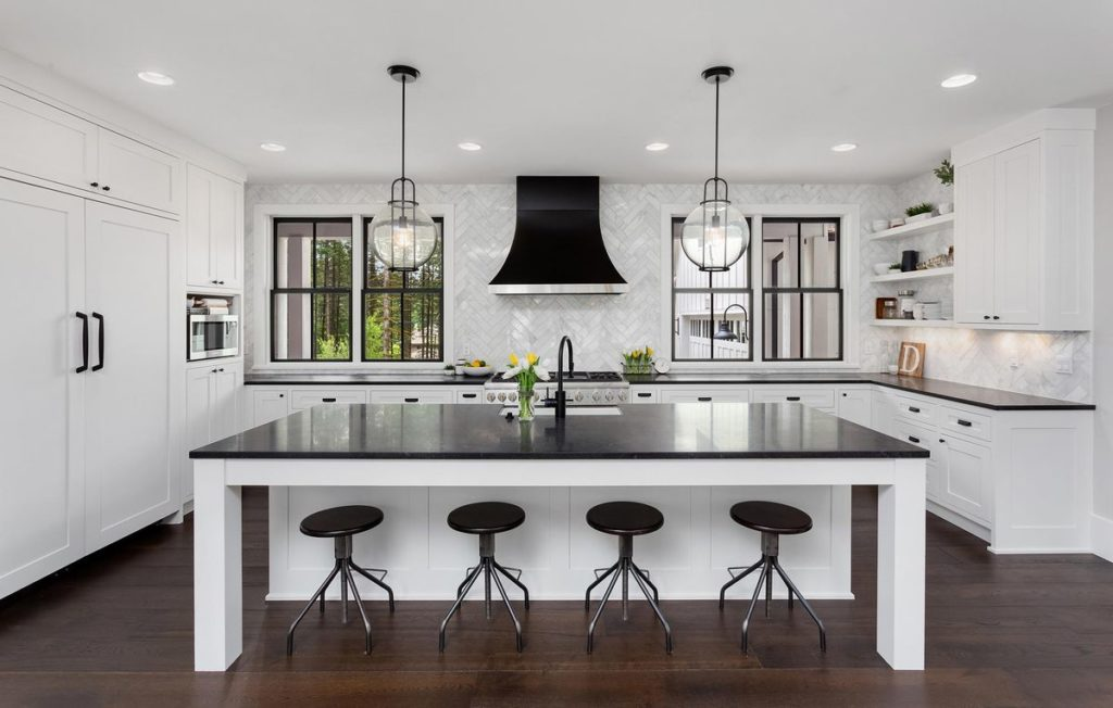 Black and white kitchen with dark quartz countertops, white cabinets, and light tile backsplash