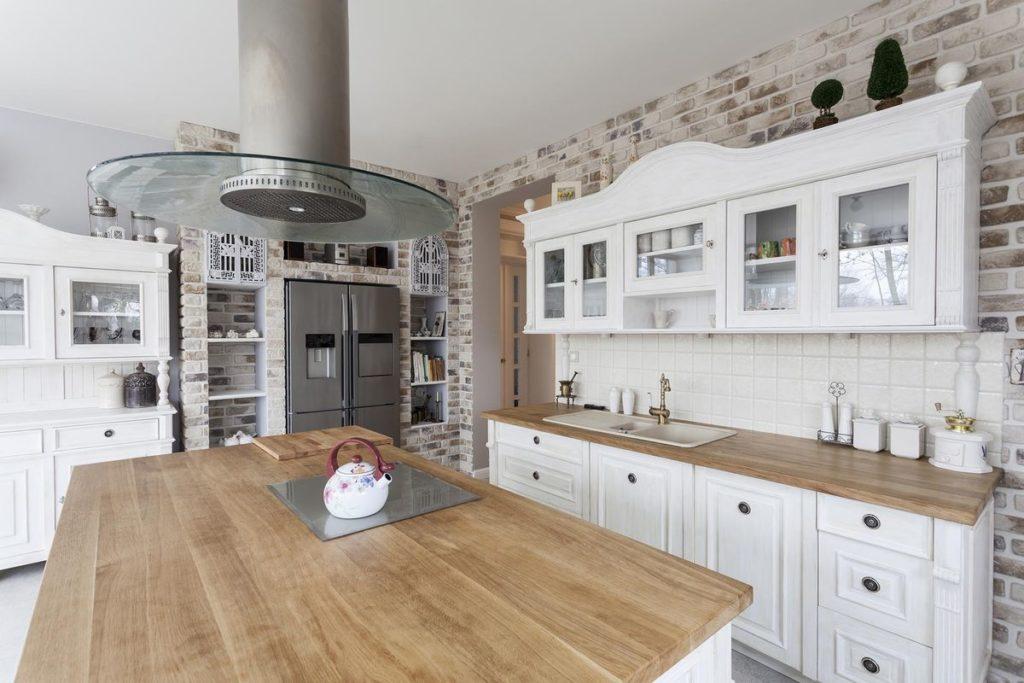 White farmhouse kitchen with butchers block countertop and tile backsplash