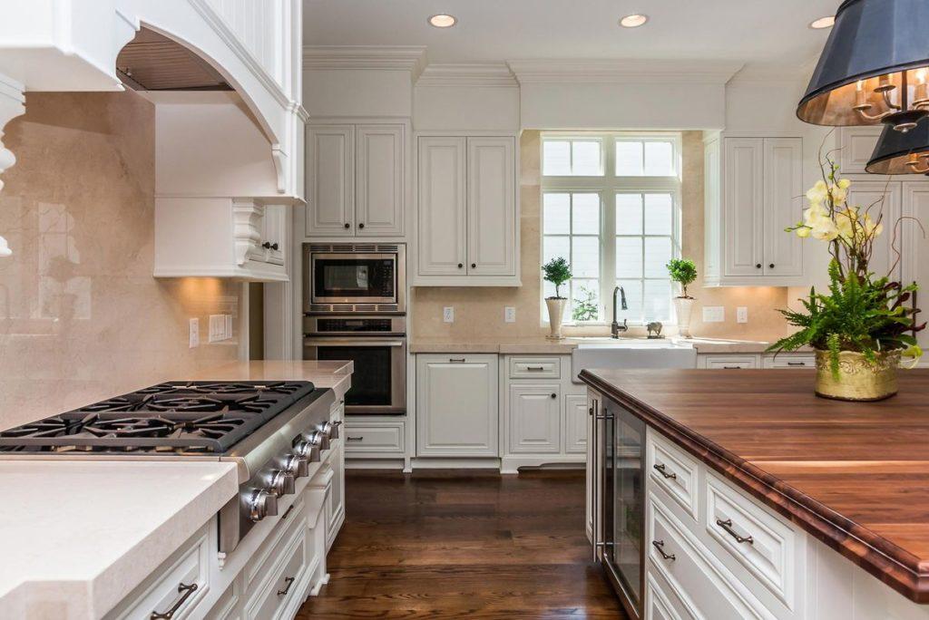 White elegant kitchen with pink granite countertops