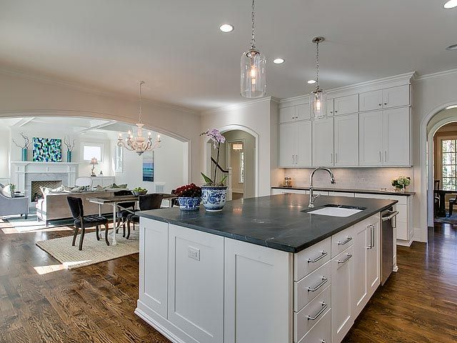 Kitchen island with built in dishwasher, white shaker cabinets, and dark granite countertop
