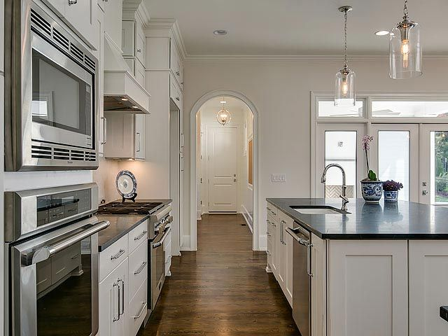 Kitchen island with white shaker cabinets and dark granite countertop