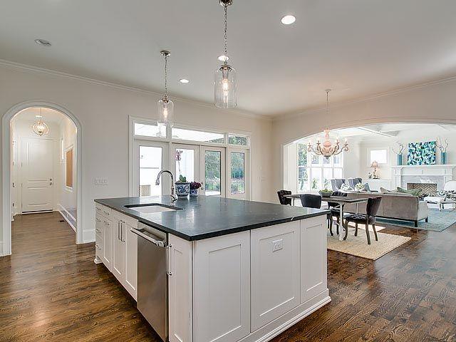 Modern kitchen island with white shaker cabinets and dark granite countertop