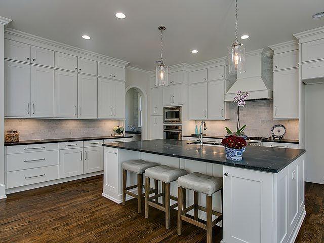 Modern kitchen with white shaker cabinets and dark granite countertops