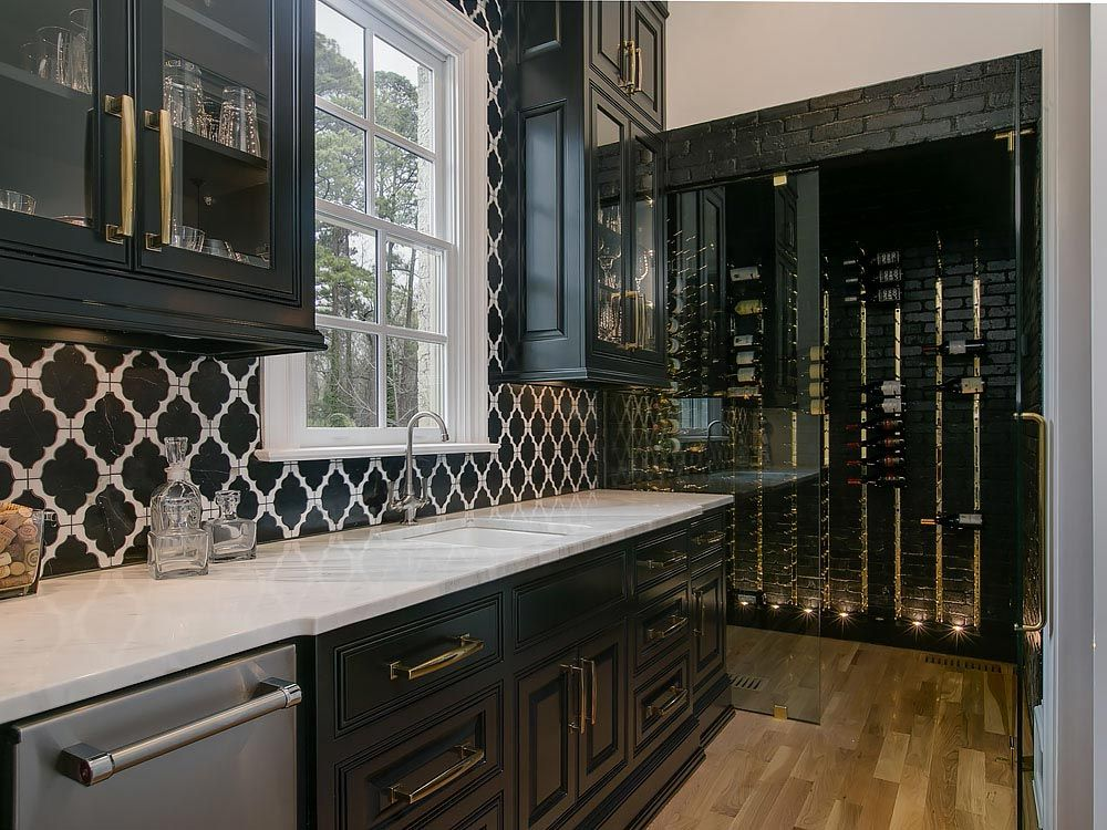 Sophisticated black cabinets with gold hardware and contrasting quartz countertop