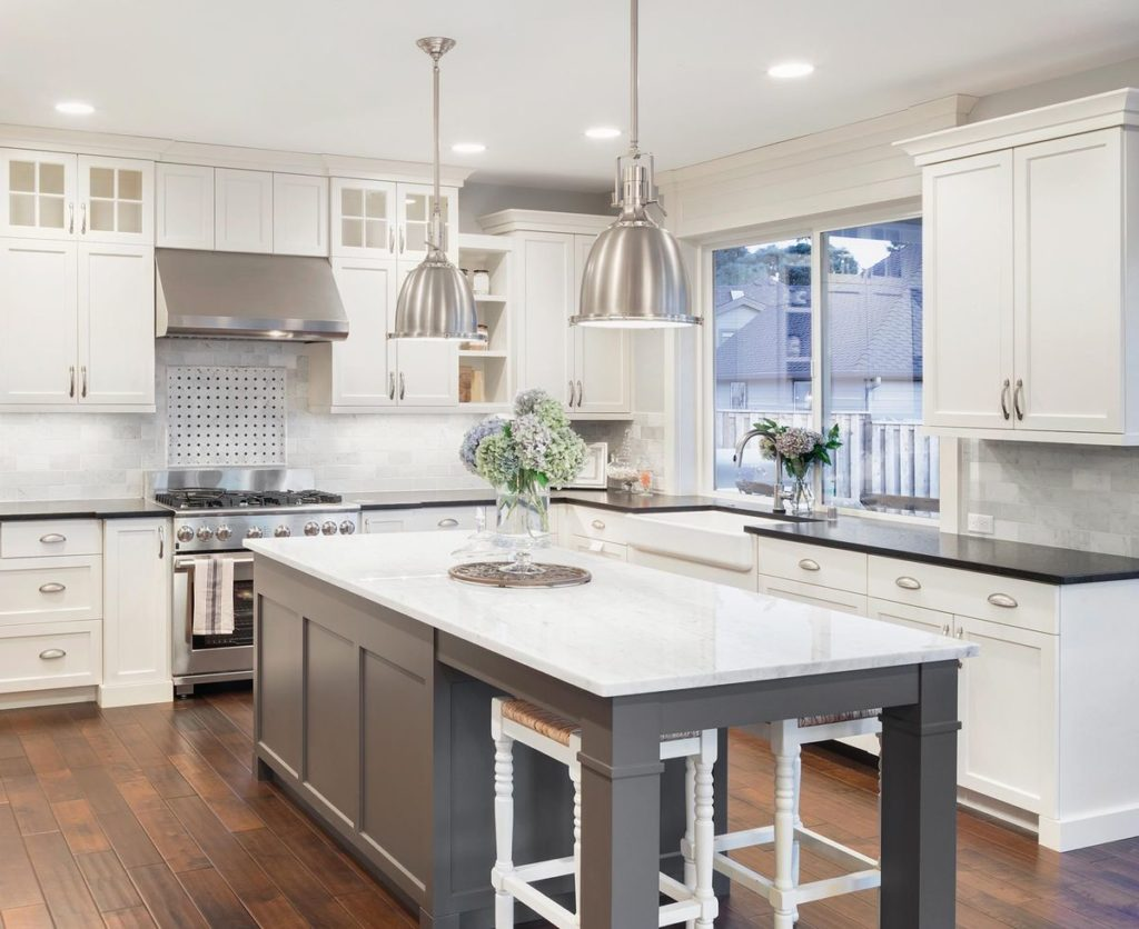 Sleek kitchen featuring white shaker cabinets and gray island with white quartzite countertop