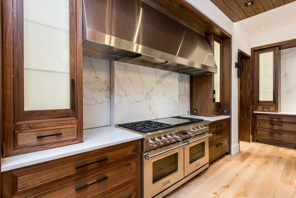 Stunning kitchen with wooden cabinets, white quartz countertops and marble backsplash