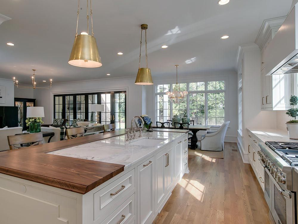 Gold pendent lights above modern island featuring split wood and white granite countertop