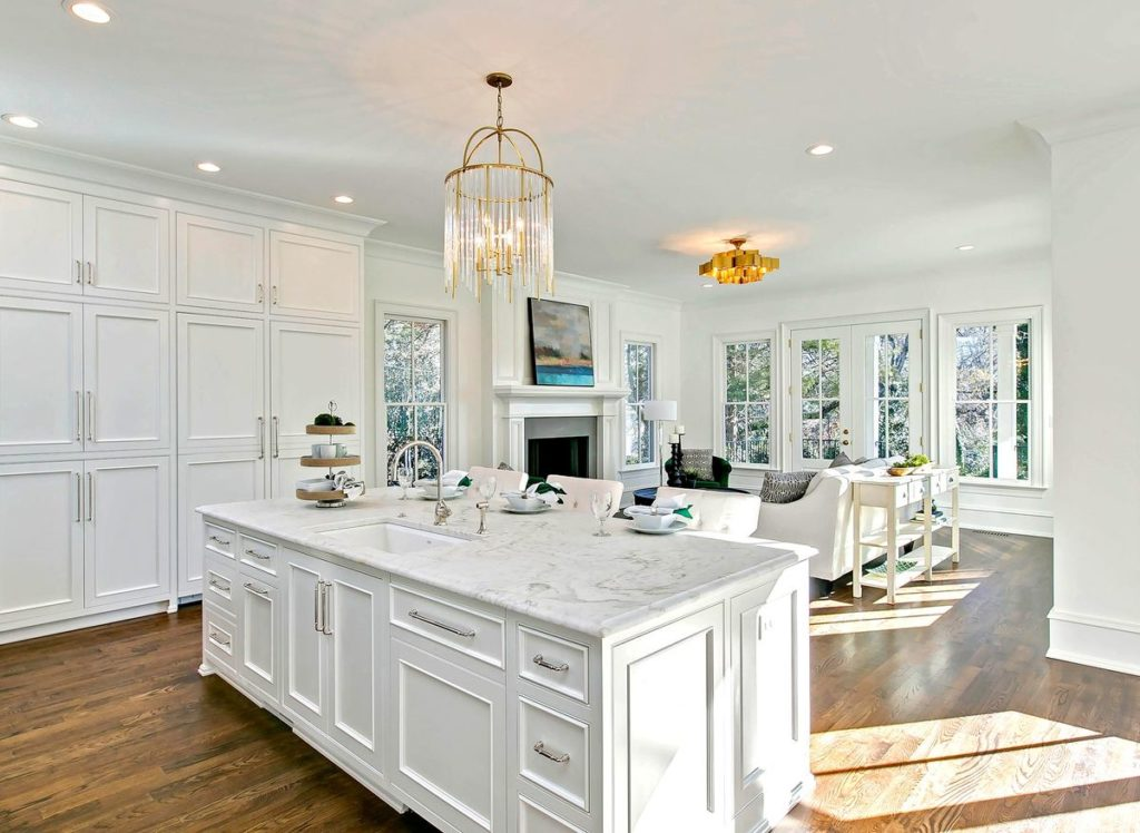 White kitchen cabinets and island with white marble countertop