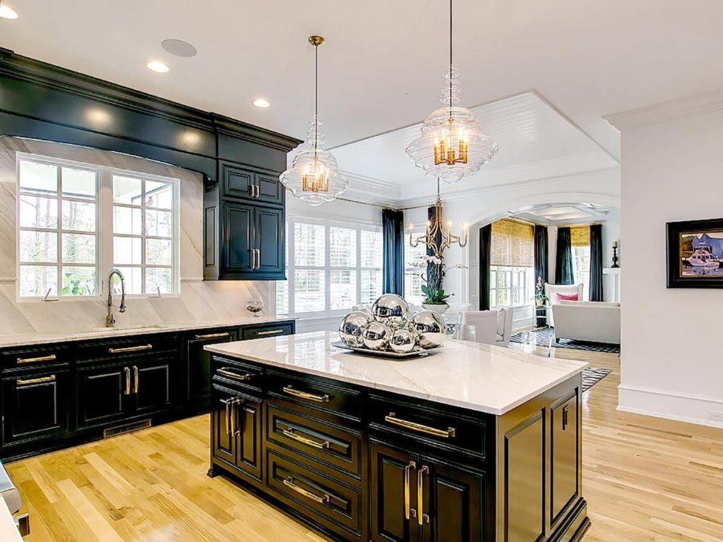 Black kitchen cabinets with gold hardware and white quartz countertops