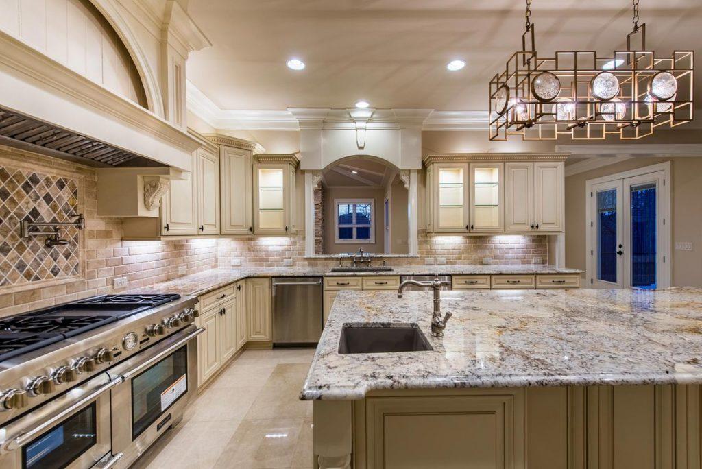 Granite kitchen island and countertops with warm porcelain tile backsplash