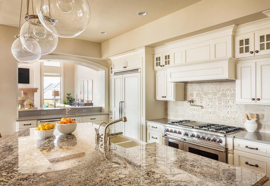 Beautiful granite topped kitchen island with integrated farmhouse 50/50 sink