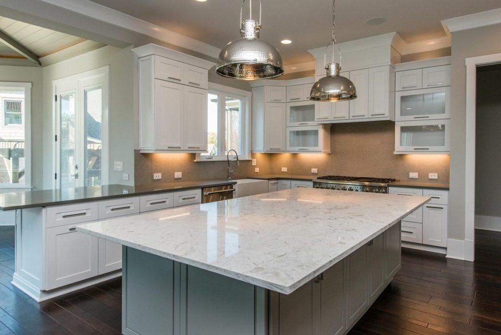 White quartz kitchen island with sage green cabinets