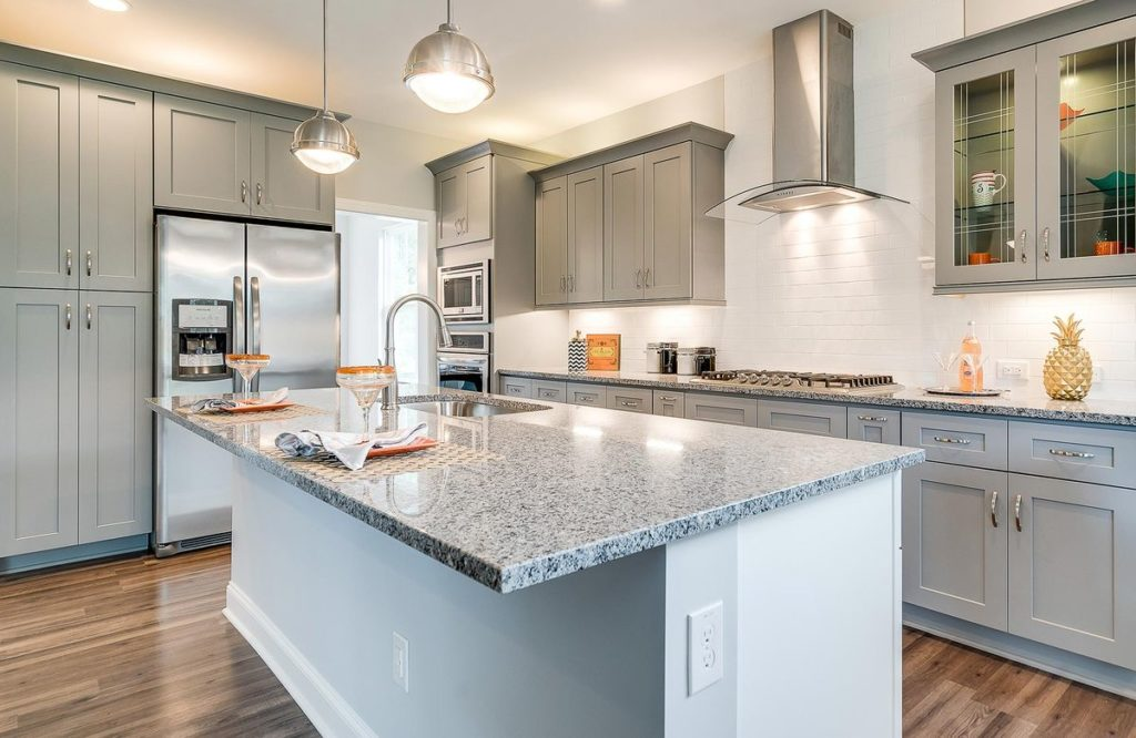 Modern kitchen with light gray cabinets and kitchen island with granite countertop