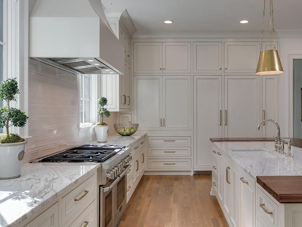 Kitchen featuring white shaker cabinets with silver hardware and white granite countertops