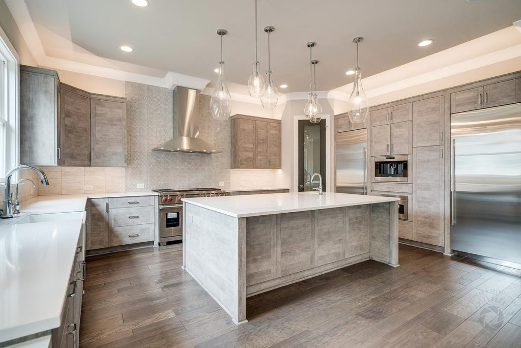 Modern kitchen with light gray cabinets, white quartzite countertops and island