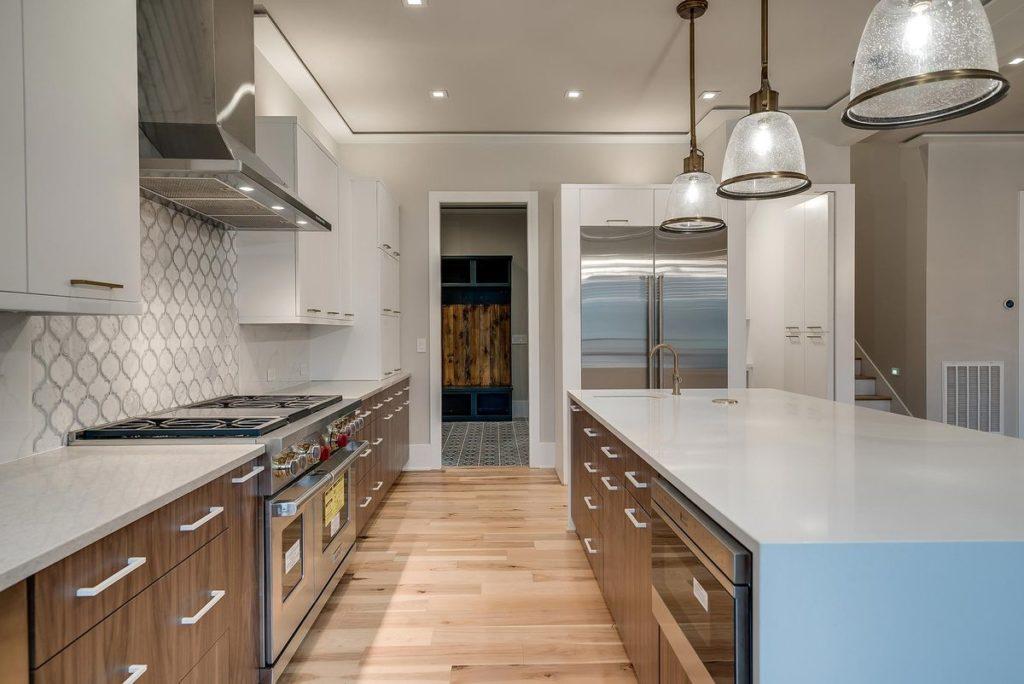 Stylish mid-century modern kitchen with split white and teak cabinets plus white quartz waterfall legged island and white quartz countertops