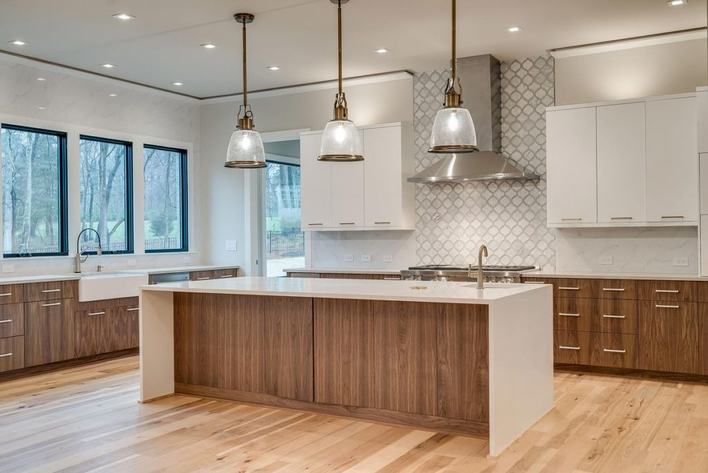 Stunning mid-century modern kitchen with split white and teak cabinets plus white quartz waterfall legged island