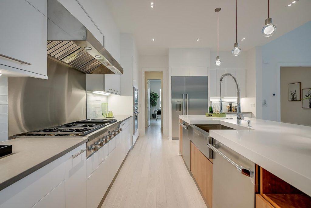 Mid-century modern kitchen with brushed wood cabinets, white quartz countertops and waterfall legged white quartz kitchen island
