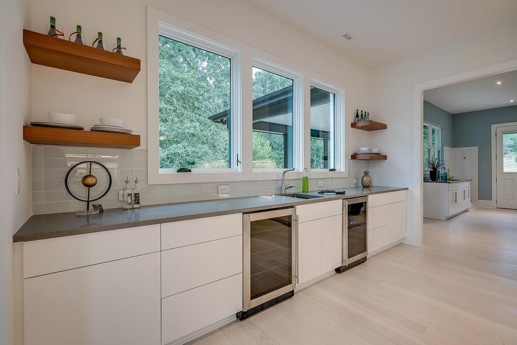 Kitchen with modern open wood shelves, white cabinets and gray soapstone counters