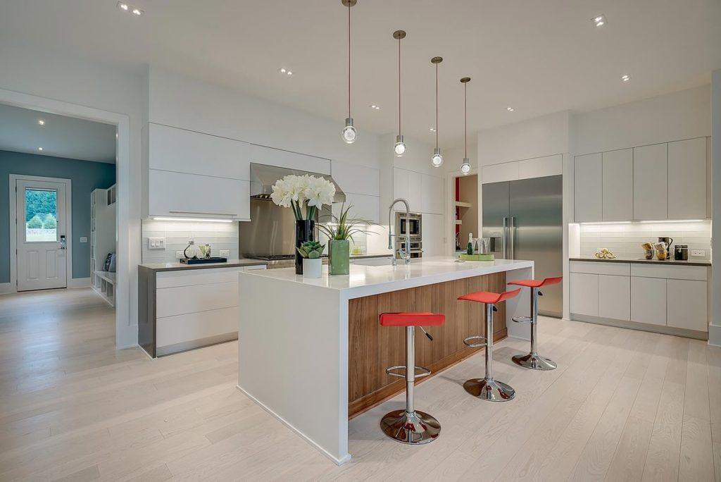 Modern kitchen with white cabinets, water fall leg white quartz kitchen island and gray quartz countertops