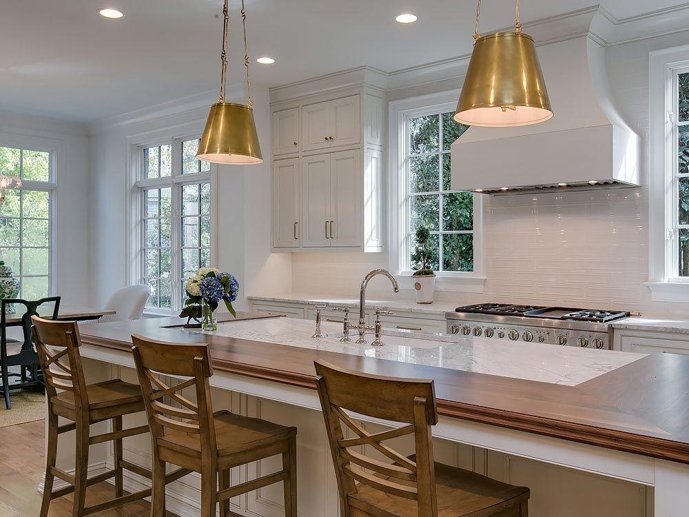 Modern kitchen island featuring split wood and white granite countertop